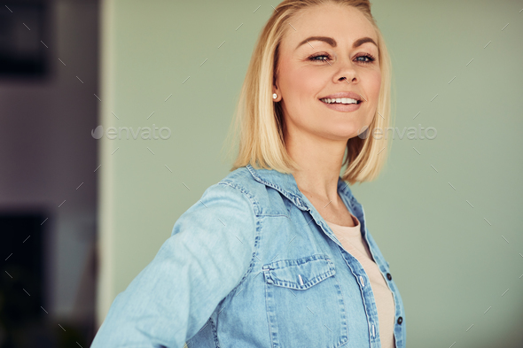 Smiling young businesswoman standing confidently in an office - Stock Photo - Images
