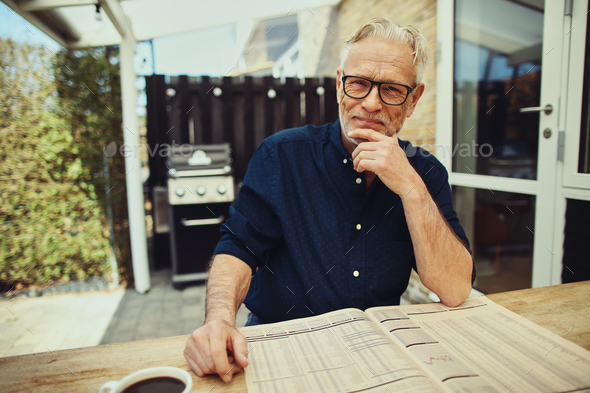 Content senior man reading a newspaper at his patio table - Stock Photo - Images