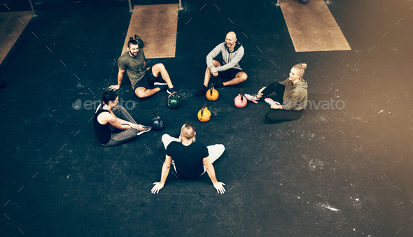 Fit people talking on a gym floor after working out - Stock Photo - Images