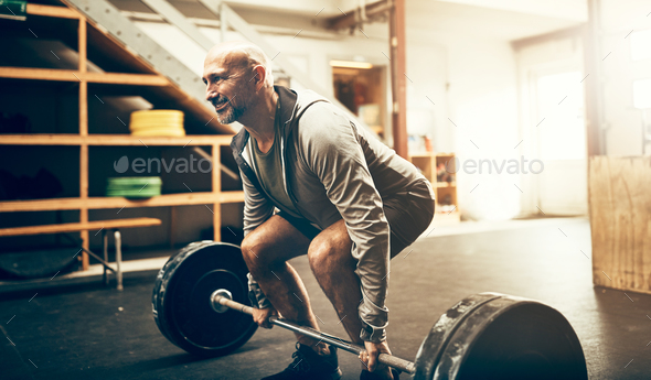 Fit mature man lifting heavy weights during a workout session - Stock Photo - Images