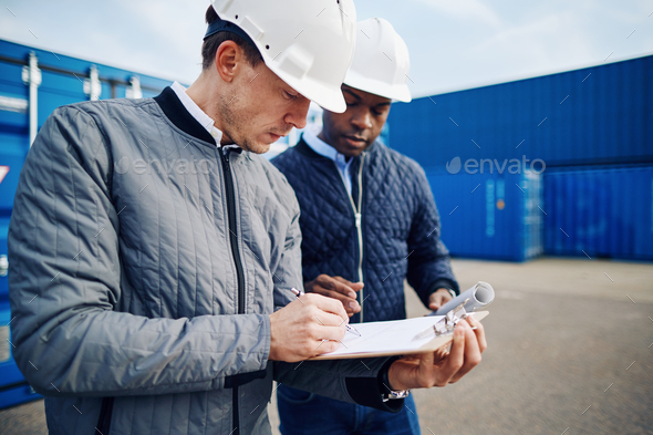 Two engineers standing in a commercial shipping yard tracking containers - Stock Photo - Images