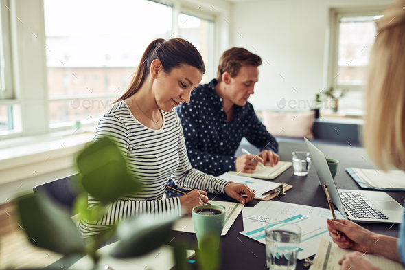 Smiling businesspeople having a meeting around an office table - Stock Photo - Images