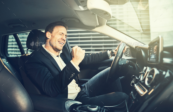 Businessman fist pumping while driving in his car in the city - Stock Photo - Images
