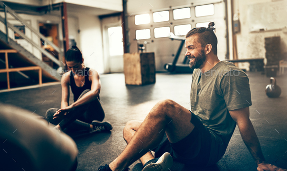 Fit people sitting on a gym floor after working out - Stock Photo - Images