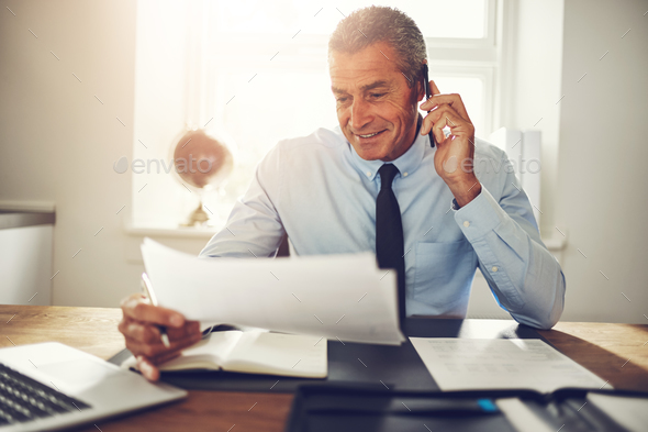 Consultant sitting at a desk discussing documents over the phone - Stock Photo - Images