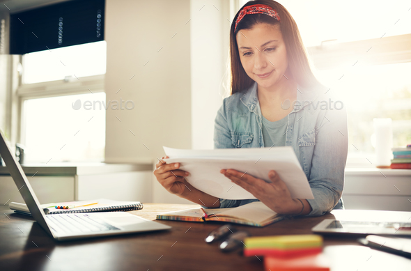 Young female entrepreneur doing paperwork at laptop - Stock Photo - Images