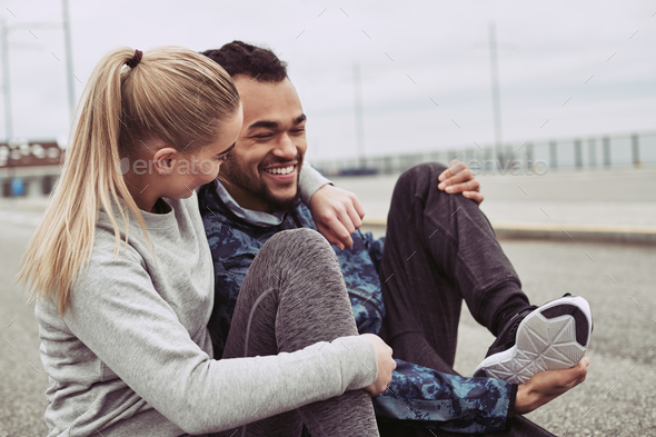 Young couple laughing while taking a break from jogging - Stock Photo - Images