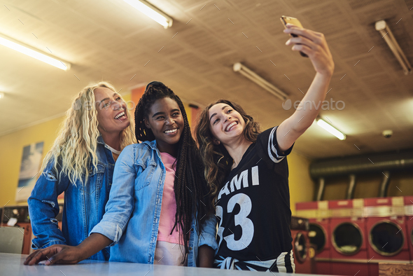 Smiling young friends standing in a laundromat taking selfies together - Stock Photo - Images