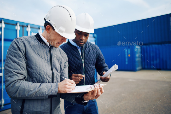Two engineers standing in a shipping yard discussing logistics - Stock Photo - Images