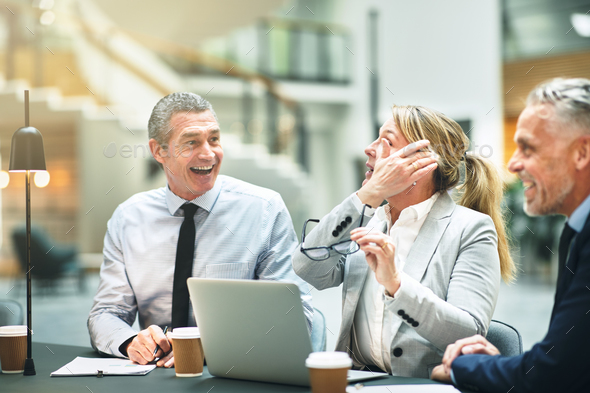 Mature businesspeople laughing while sitting together at an office table - Stock Photo - Images