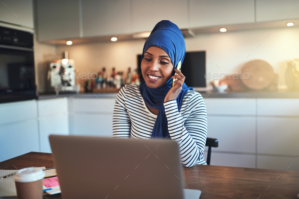 Smiling Arabic entrepreneur talking on a cellphone in her kitchen - Stock Photo - Images