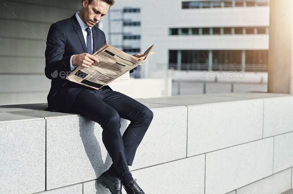 Man wearing suit sitting and reading newspaper - Stock Photo - Images