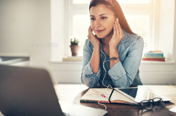 Employee woman with headphones looking at laptop in office - Stock Photo - Images
