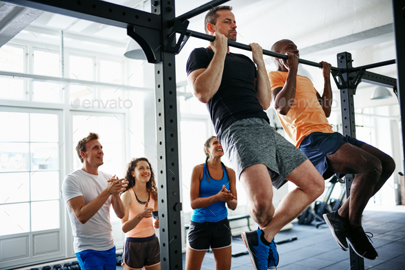 People watching two men doing pullups in a health club - Stock Photo - Images