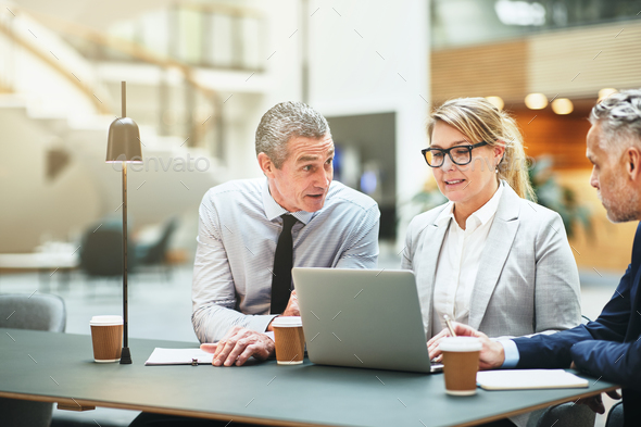 Mature businesspeople working at a table together in an office - Stock Photo - Images