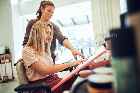 Smiling client and hairdresser choosing hair colors in a salon - Stock Photo - Images