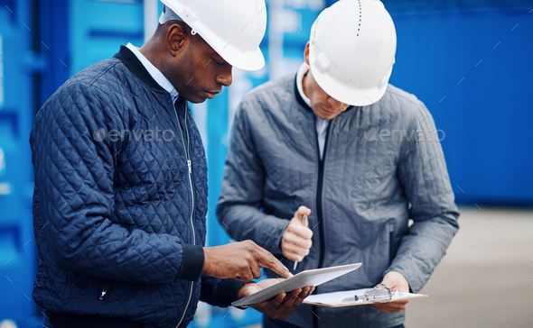 Two engineers comparing inventory lists together in a shipping yard - Stock Photo - Images
