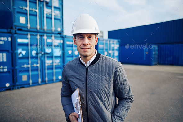 Smiling dock foreman standing in a commercial shipping yard - Stock Photo - Images