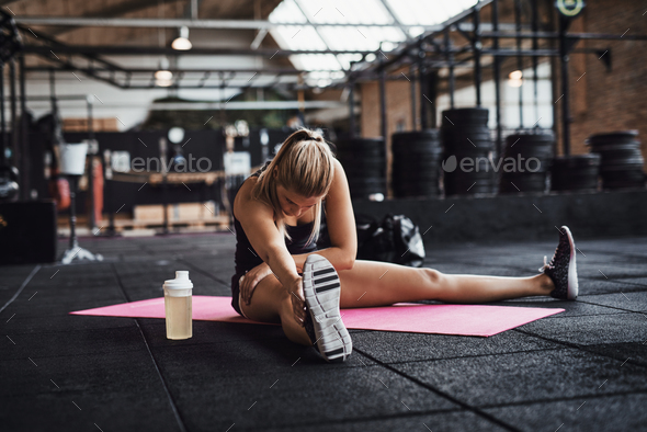 Healthy young woman stretching on the floor of a gym - Stock Photo - Images