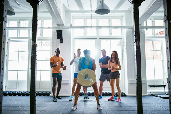 Young woman lifting weights with friends cheering in the background - Stock Photo - Images