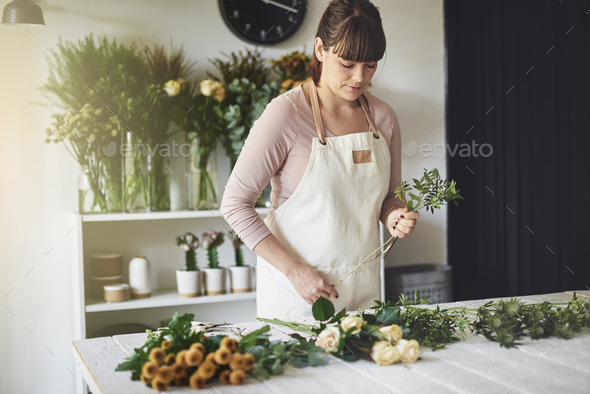 Young woman making floral arrangements in her flower shop - Stock Photo - Images