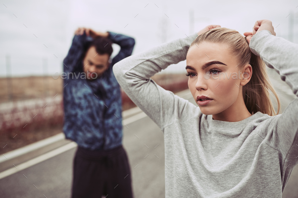 Young couple stretching together before an outdoor run - Stock Photo - Images