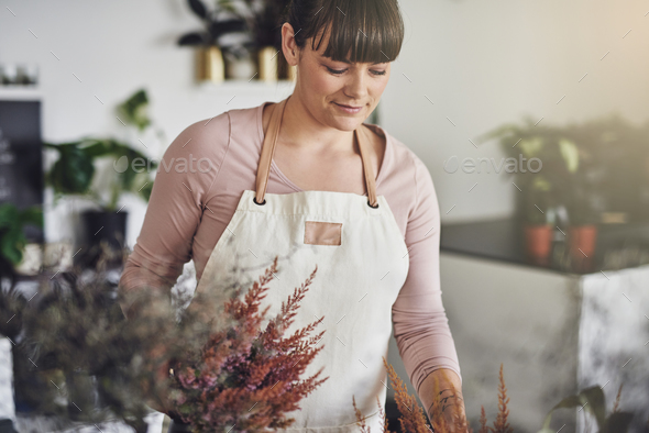 Smiling florist arranging flowers on a table in her shop - Stock Photo - Images