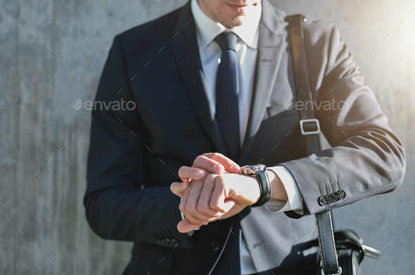 Stylish man wearing suit looks at watch - Stock Photo - Images
