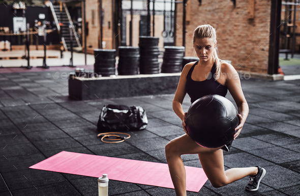 Woman working out with an exercise ball in a gym - Stock Photo - Images