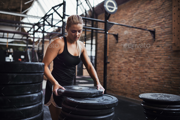 Fit young woman preparing weights before a gym workout - Stock Photo - Images