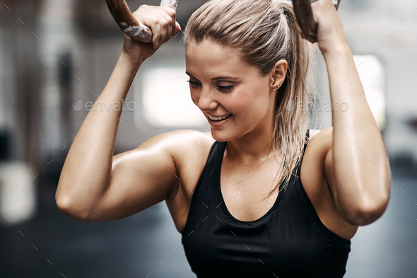 Smiling young woman working out on rings at the gym - Stock Photo - Images