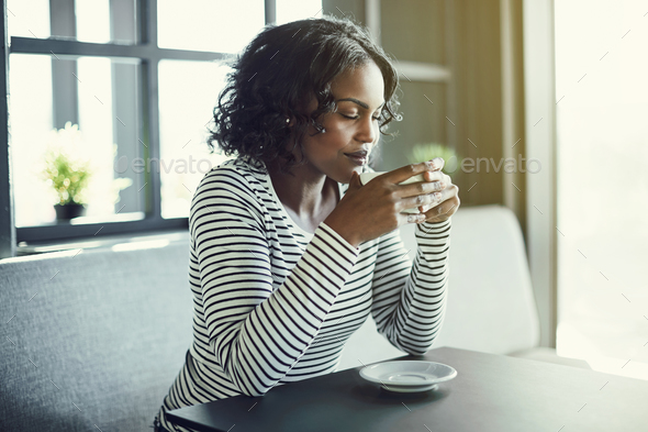 Smiling African woman enjoying the aroma of her fresh coffee - Stock Photo - Images