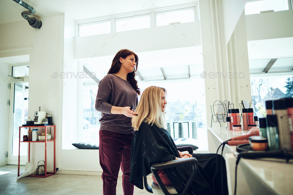 Hairdresser styling a female client's long hair in her salon - Stock Photo - Images
