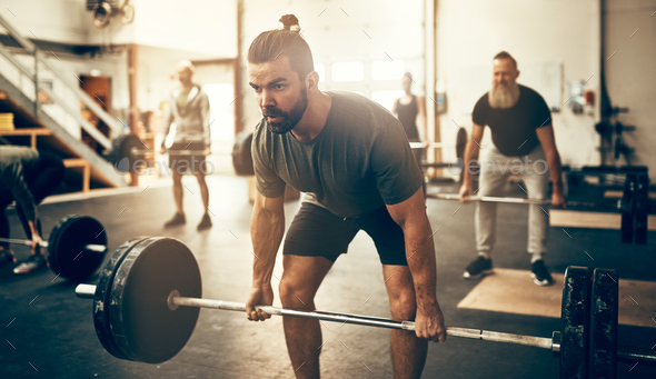 Fit young man lifting weights in a gym class - Stock Photo - Images