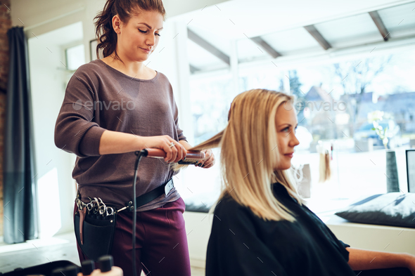 Hairdresser straightening a female client's hair in her salon - Stock Photo - Images