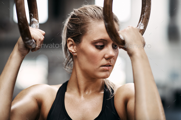 Focused young woman working out on rings at the gym - Stock Photo - Images