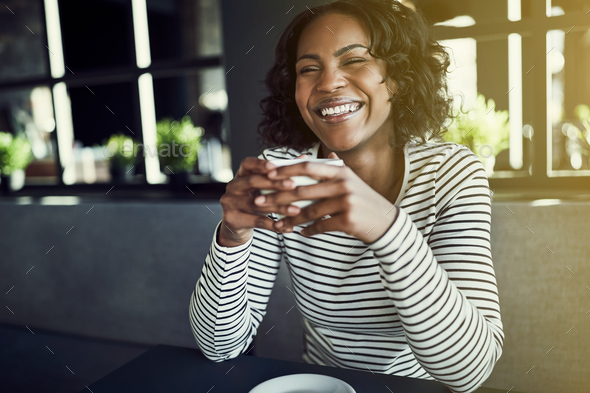 Laughing young African woman drinking fresh coffee in a cafe - Stock Photo - Images