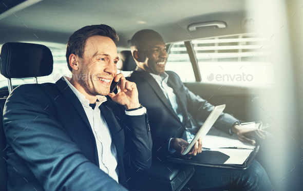 Two smiling colleagues working together while driving in the city - Stock Photo - Images