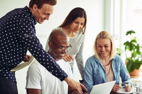 Diverse businesspeople smiling and working on a laptop together - Stock Photo - Images