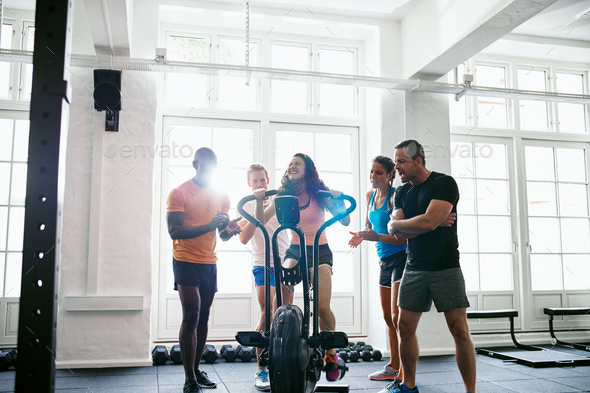 Frinds encouraging a woman riding a bike in the gym - Stock Photo - Images