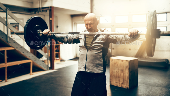 Mature man preparing to drop his barbell at the gym - Stock Photo - Images