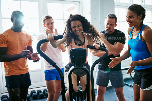 People supporting their friend riding a gym stationary bike - Stock Photo - Images