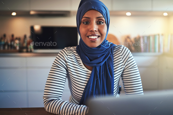 Smiling Arabic female entrepreneur using a laptop in her kitchen - Stock Photo - Images