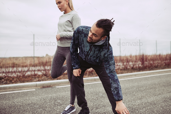 Young couple stretching before jogging on a country road - Stock Photo - Images