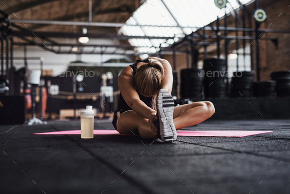Fit young woman doing stretches on a gym floor - Stock Photo - Images
