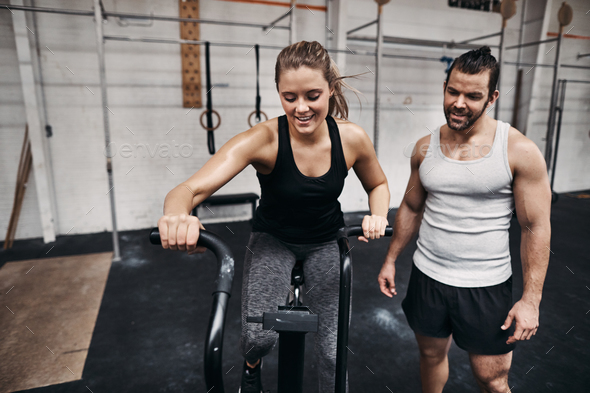 Fit woman riding a stationary bike with her gym partner - Stock Photo - Images