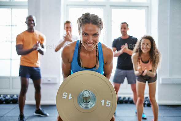 Smiling woman lifting weights with friends clapping in the background - Stock Photo - Images
