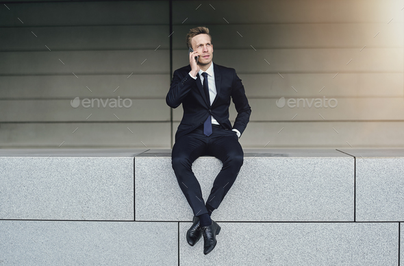 A businessman with legs crossed speaks phone - Stock Photo - Images