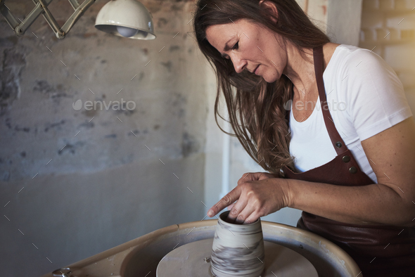 Female artisan creatively sculpting clay in her pottery studio - Stock Photo - Images