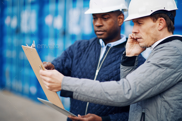 Engineers discussing an inventory together in a commercial freight shipyard - Stock Photo - Images
